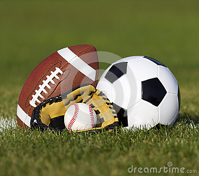 Sports balls on the field with yard line. Soccer ball, American football and Baseball in yellow glove on green grass