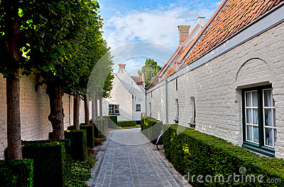 Street with medieval houses and trees in Bruges / Brugge, Belgium