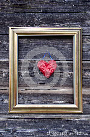 Golden picture frame on old wooden wall and heart