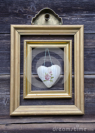 Golden picture frame on wooden wall and cloth heart