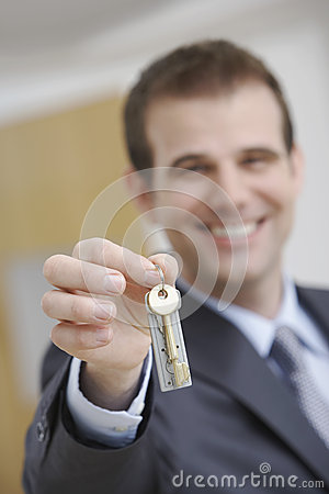 Real Estate Agent Holding Out House Key