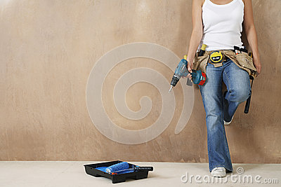 Woman With Toolbelt And Drill Leaning Against Wall