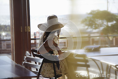 Woman Wearing Sunhat At Cafe