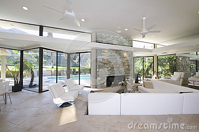 Seating Area And Stone Fireplace In Spacious Living Room With Pool View