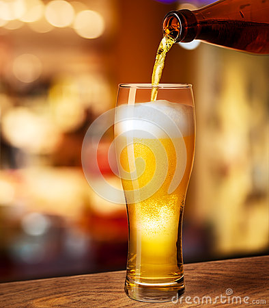 Pouring beer in glass on bar desk