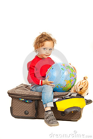 Toddler boy with globe sitting on luggage