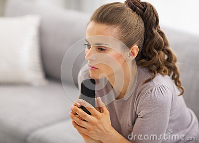 Concerned woman sitting on sofa and holding mobile phone in hands