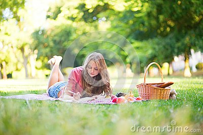 Girl having a picnic and writing in her diary