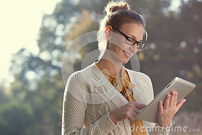 Happy woman in glasses using tablet pc