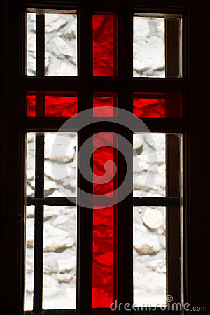 Stained window with red cross in a church