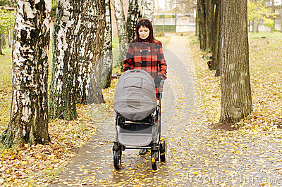 Woman walking in autumn park with baby buggy