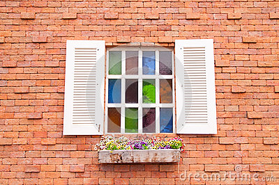 Beautiful wood window with multi color glass and brick wall