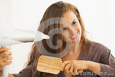 Woman brushing and blow drying hair in bathroom