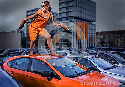 Playful stylish girl in orange overalls standing on car roof in the parking lot