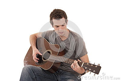 Young man playing acoustic guitar sitting