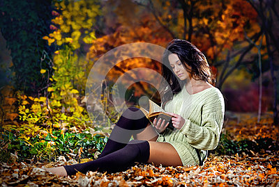 Young caucasian sensual woman reading a book in a romantic autumn scenery.Portrait of pretty young girl in autumnal forest