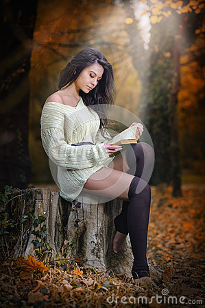 Young Caucasian sensual woman reading a book in a romantic autumn scenery. Portrait of pretty young girl in the forest in autumn