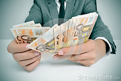 Man in suit with counting euro bills