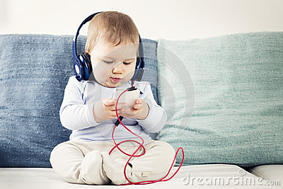 Baby boy listening music at earphones with iphone in hands.