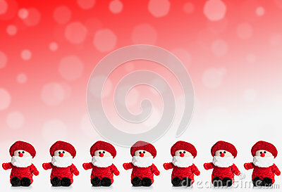 Row of puppets of Santa Claus on a red background with snow