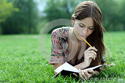 Beautiful woman lays on a grass in park with a diary in ha