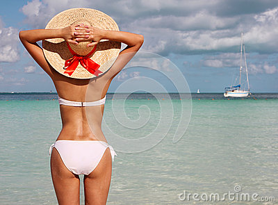 girl on tropical beach. Beautiful young woman with sun hat