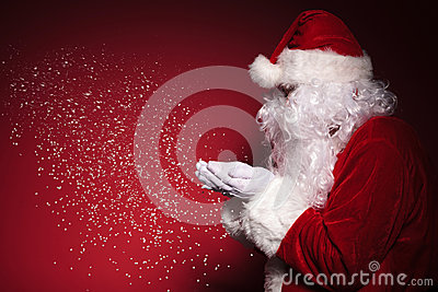 Side view of santa claus blowing snow