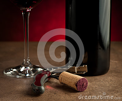 Stopper on corkscrew near bottle and wine glass