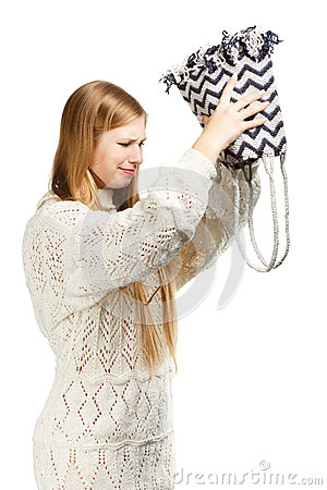 Young woman shaking out her bag in search