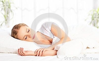 Beautiful woman sleeping and smiles in his sleep in  bed