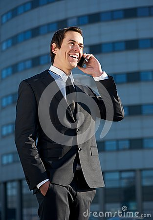 Smiling business man talking on mobile phone outdoors