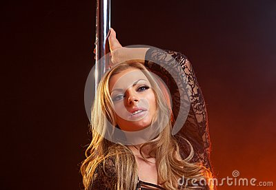 Portrait of a sensual female with blond hair with dance pole