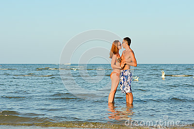 Young happy couple together on sandy beach embracing outdoors