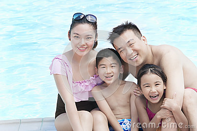Family portrait, mother, father, daughter, and son, smiling by the pool