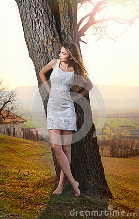 Beautiful girl portrait with hat near a tree in the garden. Young Caucasian sensual woman in a romantic scenery. Girt in white