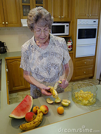 Elderly Lady Preparing Fruit Salad.