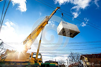 Mobile crane operating by lifting an electric generator