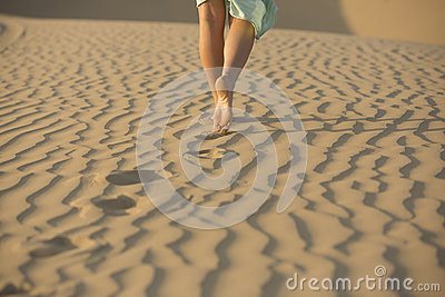 Barefooted woman walks in the sand of desert