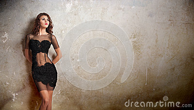 Charming young brunette woman in transparent lace black dress leaning against an old wall. Sexy gorgeous young woman near old wall