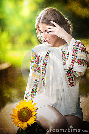 Young girl wearing Romanian traditional blouse holding a sunflower outdoor shot. Portrait of beautiful blonde girl