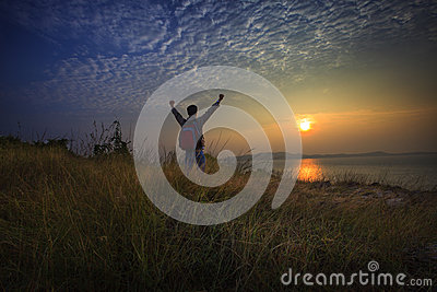 Young man standing and rising hand as victory on grass hill looking to sun above sea horizontal with dramatic colorful sky backgro