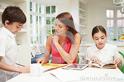 Mother Helping Children With Homework Using Tablet