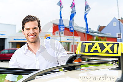 Driver in front of taxi waiting for clients