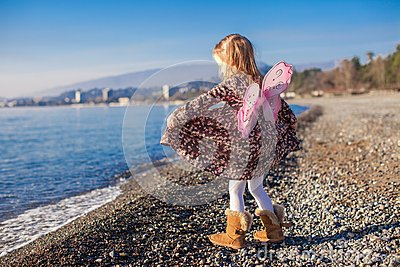 Adorable little girl with butterfly wings running