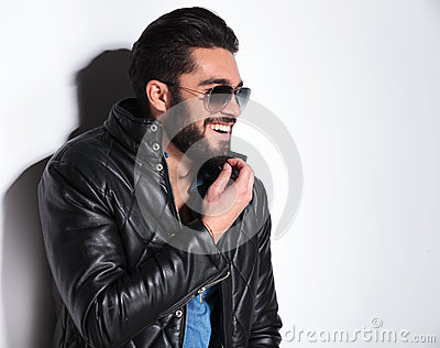 Laughing man in leather jacket  pulling his beard