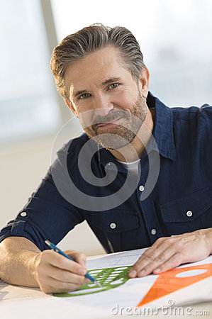 Male Architect Working On Blueprint At Desk