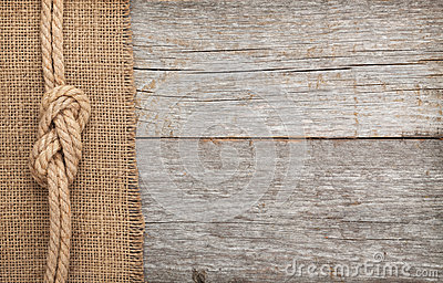 Ship rope on wood and burlap texture background