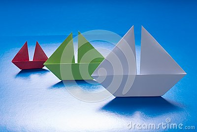 Paper Ships Sailing on Blue paper sea. Origami Boat. Paper Sea