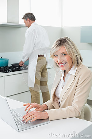 Woman using laptop and man cooking food in kitchen