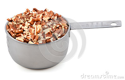 Chopped pecan nuts in a metal cup measure